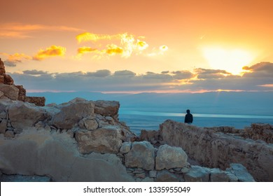 Sunrise over Masada fortress and Dead sea. Silhouette of man looking at magical sunset.  Israel