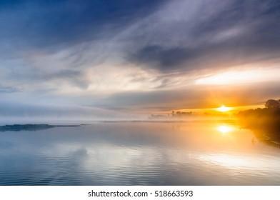 Sunrise over a misty wild river