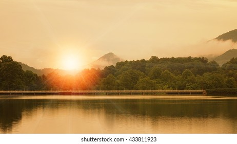 Sunrise over mountain lake with mist