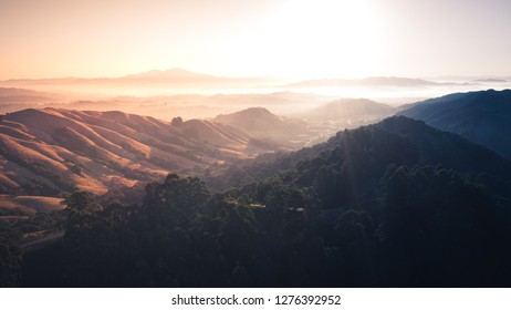 Sunrise over a mountain landscape.  Berkeley hills glowing with sun rays with Mount Diablo in the distance.