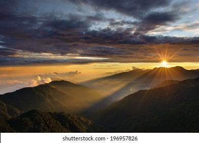 A sunrise over the mountains on a cloudy morning.