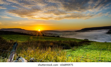 sunrise over the mountains in Yorkshire dales. showing the sun rising and the mist over the valley.