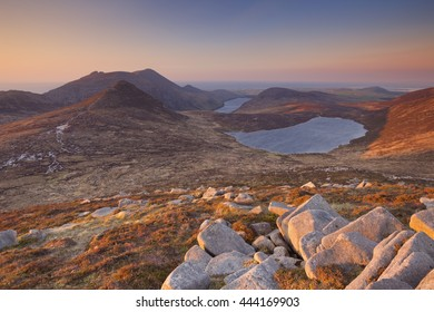 Sunrise over the Mourne Mountains and lakes in Northern Ireland. Photographed from the peak of Slieve Loughshannagh.