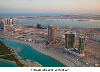 Sunrise over new districts of Abu Dhabi (capital of United Arab Emirates) at the coast of Persian Gulf. Road and building construction. Persian Gulf at far horizon.