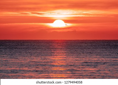 Sunrise over the ocean. Beautiful seascape. Orange sky reflecting on water at dawn. Spiritual new day dawning natural world background image.