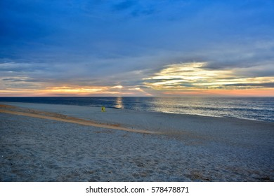 Sunrise Over the Ocean with Empty Lifeguard Stand on the Beach