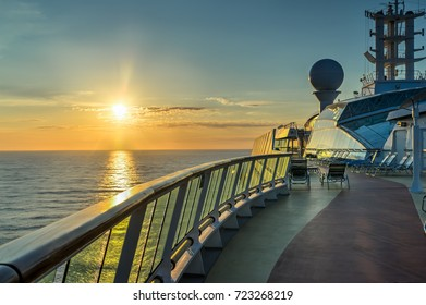 Sunrise over the ocean horizon from the cruise ship with reflections along the glass railing