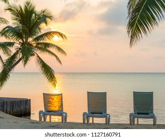 Sunrise over the ocean on dream beach vacation with palmtrees and deckchairs