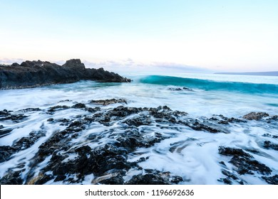 Sunrise over the Pacific Ocean with waves crashing on the Rocky Shoreline under a blue sky on the North Shore of the Hawaiian island of Oahu