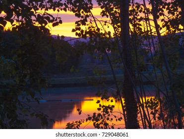 Sunrise over a pond showing tree silhouettes on an October morning in the north west