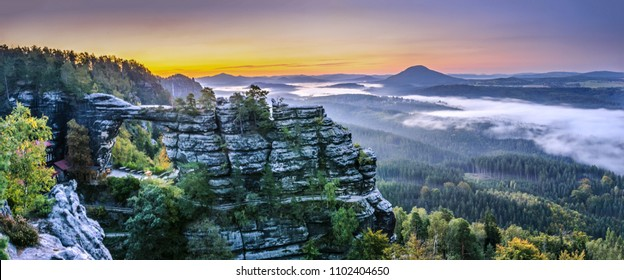 Sunrise over Pravcicka brana sandstone arch, Bohemian Switzerland National Park. Wide angle panorama photo of landscape with famous arch during daybreak with colorful sky and morning fog in valley.