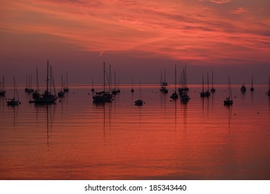 Sunrise over a protected New England Harbor dotted with sail boats on a peaceful summer  morning