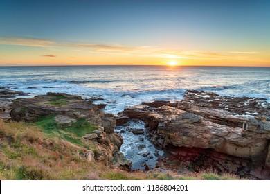 Sunrise over rock ledges at Howick on the Northumberland coastline