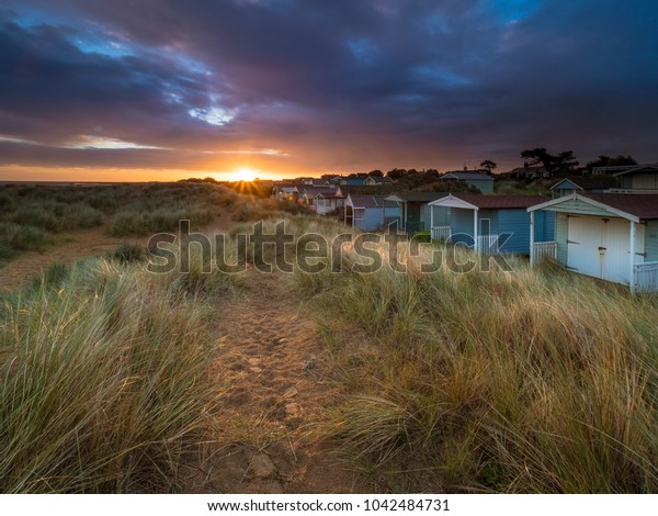 Sunrise over the sand dunes and beach huts of Old Hunstanton.