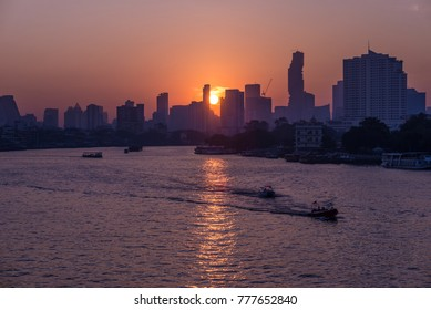 Sunrise over the scenic skyline at Bangkok, Thailand, viewed in backlight at sunrise with orange red clear sky. Boats cruising on the Chao Phraya River.