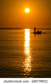 sunrise over the sea and the boat with the fishermen