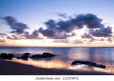 Sunrise over the sea with the sun's reflection in the wet sand