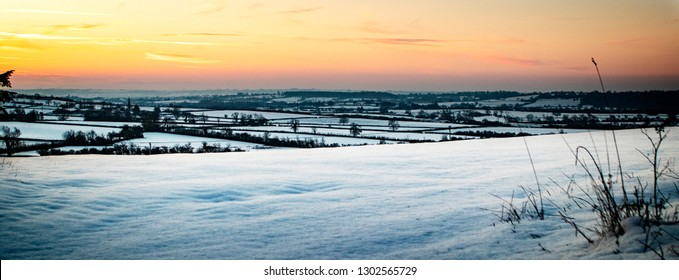 Sunrise over a snow covered landscape, in Brinkworth, Wiltshire