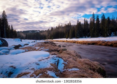 The sunrise over the snowy landscape and the beautiful romantic stream
