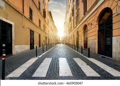 Sunrise over street with pedestrian crossing in Rome