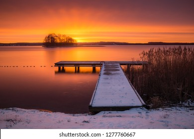 Sunrise over the Swiecajty lake and wooden footbridge near Wegorzewo, Masuria, Poland