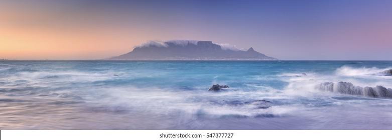 Sunrise over the Table Mountain and Cape Town from the beach of Bloubergstrand.