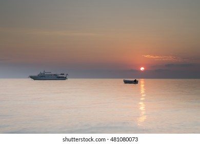 Sunrise over tranquil calm seas with boats