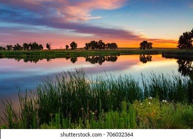 The sunrise paints the sky over Lake Ladora on a summer morning at Rocky Mountain Arsenal National Wildlife Refuge in Denver, Colorado