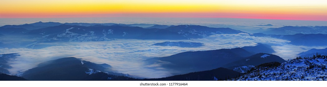 Sunrise panorama from the top of mountains, clouds or fog in the valley