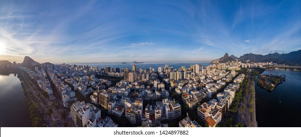 Sunrise panoramic aerial view of Rio de Janeiro with Ipanema neighbourhood in the foreground and city lake and cityscape with Corcovado mountain in the background against a blue sky
