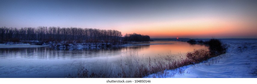 Sunrise panoramic HDR view of the river Jiu and its frozen valley on the day of winter solstice (shortest day of the year, Romania, Dolj County).