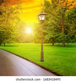 Sunrise in park with pedestrian walkway and lantern