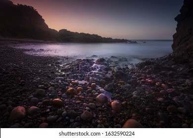 Sunrise and pebbles at Rotherslade, a small Bay in South Gower next to a more famous one, Langland Bay on the Gower peninsula in Swansea, South Wales, UK