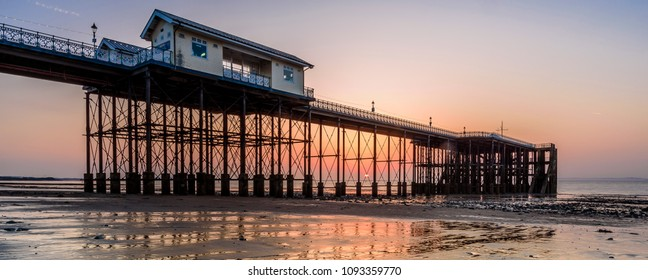 Sunrise at Penarth Pier. Penarth is a coastal town in South Wales, UK, near Cardiff the capital of Wales. The pier is a fine example of Victorian architecture