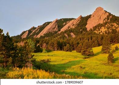 A sunrise photo of the Flatirons at Chautauqua Park in Boulder, Colorado