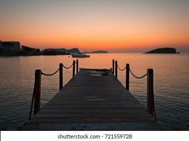 sunrise at the pier of Es Canar beach, Ibiza, Spain