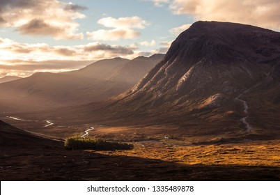 Sunrise pierces through a Scottish Highland valley in mid Autumn, illuminating a remote mountain hut.