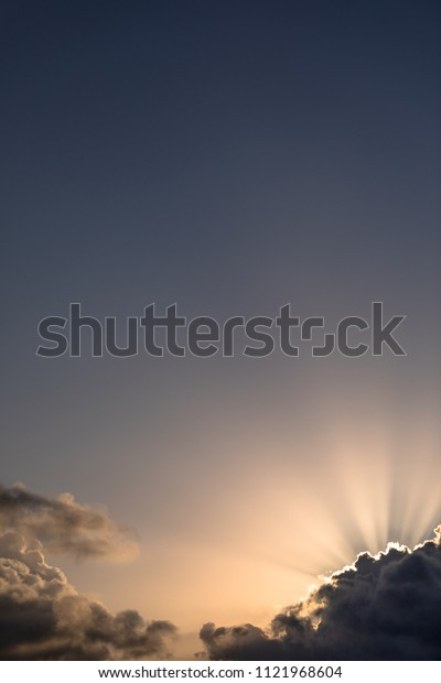 Sunrise with rays, clouds, and blank space.