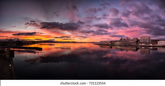 Sunrise with a red pink and purple sky in Hobart Tasmania on a winter day. The sky reflects in the water.