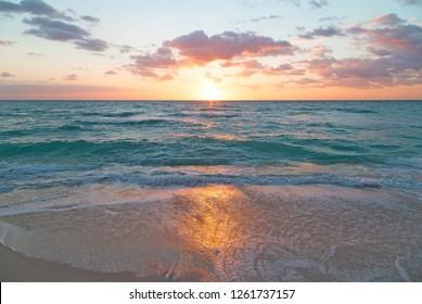Sunrise reflection on a beach sand. Golden sunrise at Miami Beach, Florida, USA.