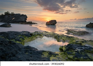 Sunrise reflections into a  lava formed natural pool in Bermuda