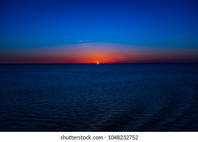 Sunrise, right as the sun breaks the horizon. Vibrant blue and orange colors fill the sky