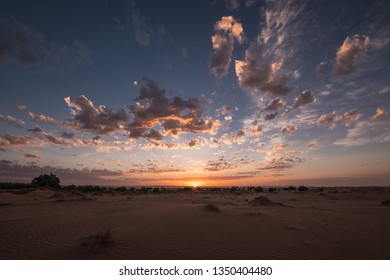 Sunrise in the Sahara desert under a beautiful blue and cloudy sky in Erg Chebbi, Morocco