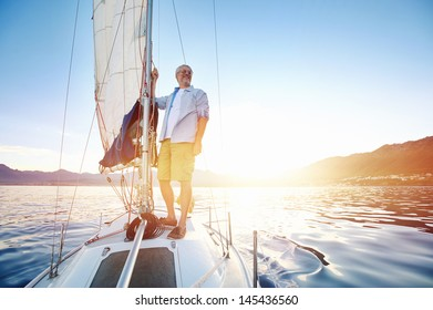 sunrise sailing man on boat in ocean with flare and sunlight on calm morning on the water