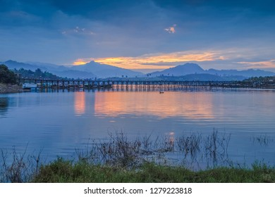 sunrise at Sangkhlaburi, river view morning of old wooden bridge (Mon Bridge) with reflection on the water, mountain and cloudy sky background, Sangkhla Buri, Kanchanaburi, western of Thailand.