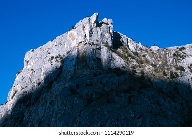 Sunrise in Sarca valley dropping shadow on Monte Colodri in Arco, northern Italy