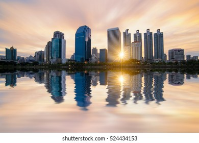 Sunrise scence of modern office buildings and condominium in Bangkok city downtown with sunrise sky and clouds at Bangkok , Thailand. And Reflection on Lake.