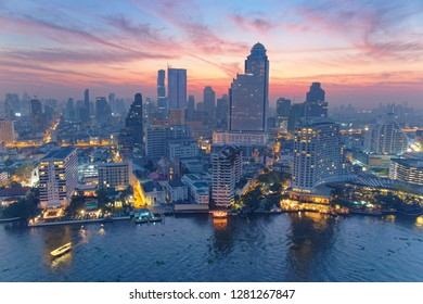Sunrise scene of Bangkok City in bird's eye view~ Aerial panorama of Bangkok in morning twilight, with rosy clouds in the dawning sky, ferry boats on Chao Phraya River & modern skyscrapers in downtown