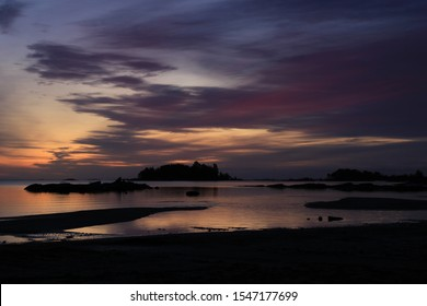 Sunrise scene at the shore of Lake Vanern, largest Lake of Sweden and the European Union. Rock formation and small island.