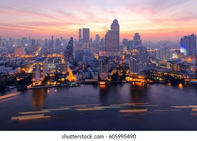 Sunrise scenery of Bangkok City in bird's eye view~ Aerial panorama of Bangkok in morning twilight, with rosy clouds in the sky, light trails on Chao Phraya River & modern skyscrapers by the riverside
